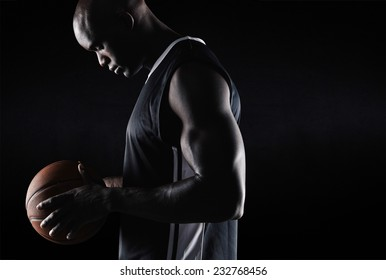 Side view of fit young basketball player holding ball against black background with copy space. African american basketball player with ball.