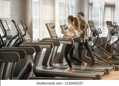 Side view of fit young man and woman smiling while running side by side on modern electric treadmills at the gym