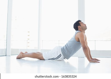Side view of a fit young man doing the cobra pose in a bright fitness studio