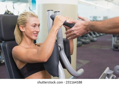 Side view of a fit young woman using fitness machine at the gym