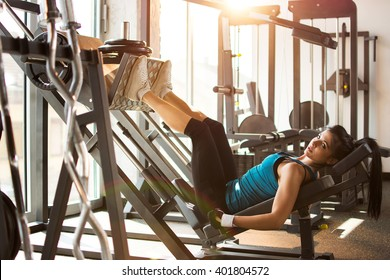 Side view of a fit young woman doing leg presses in the gym.