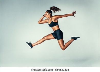 Side view of fit young woman jumping against grey background. Female model in sports wear jumping in air.