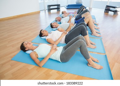 Side view of fitness class resting on mats in row at yoga class