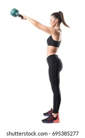 Side view of fitness gym woman doing kettlebell swing training in high position. Full body length portrait isolated on white studio background