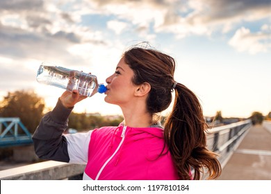 Side view of fitness woman drinking water at sunset