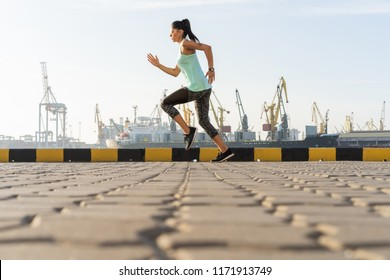 Side view of fitness woman running on a road by the sea near the sea port. Sportswoman training on seaside promenade at sunset.