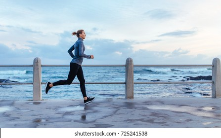 Side view of fitness woman running on a road by the sea. Sportswoman training on seaside promenade.