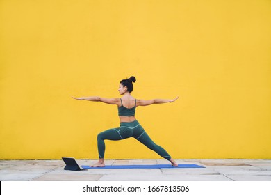 Side view of focused calm female in sportive outfit concentrating in warrior pose on yoga mat with yellow background behind