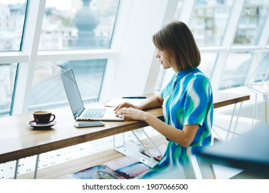 Side view of focused female remote worker with short hair browsing netbook and looking at screen while sitting with coffee cup in light workspace