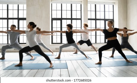 Side view focused fit young mixed race diverse people beginners standing barefoot on mat in warrior II second position, enjoying yoga morning training master class together in modern studio club.