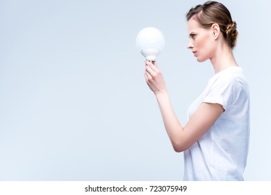 side view of focused woman holding light bulb, isolated on white