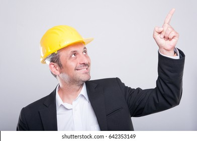 Side view foreman wearing hardhat pointing up and smiling on grey background