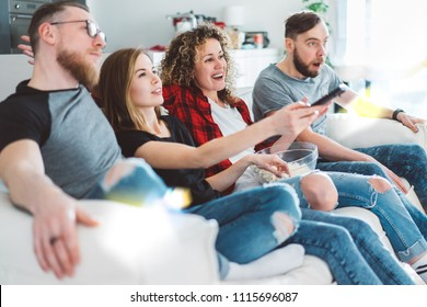 Side view of four friends sitting on sofa and watching tv in cozy light colored living room. Two young couples enjoying their day off spending it together.