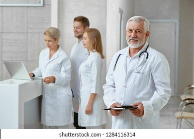 Side view of four specialists in medical clinic. Man in white uniform with stethoscope holding documents smiling and looking at camera. Man and women behind him talking discussing patients treatment .