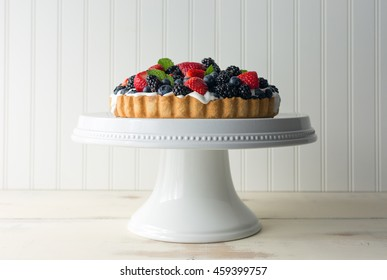 Side view of a fresh berry tart, or open faced pie, on a white ceramic cake pedestal. Made with organic whipped cream, strawberries, blueberries and blackberries.
