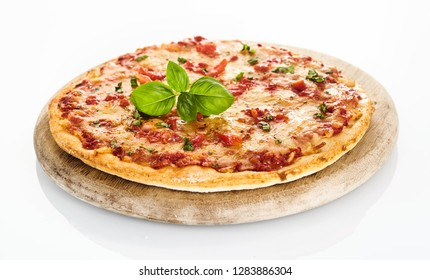 Side view of freshly baked Margherita pizza served on round wooden cutting board on white background