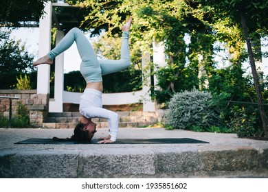 Side view full body attractive young female in sportswear doing headstand exercise with splits on mat while practicing yoga in summer park