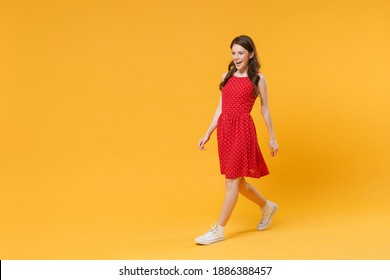 Side view full body length of beautiful young brunette woman in red summer dress walking go isolated on yellow background studio portrait. People lifestyle concept. Mock up copy space. Looking aside
