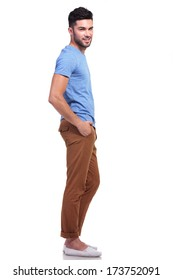 side view full body picture of a young casual man with hands in his pockets looking at the camera