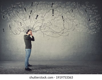 Side view full length of pensive and fatigue man suffers headache, pointing hands to temples. Guy has anxiety, mental health problems. Mess in head and pain feeling. Hard thinking, difficult task