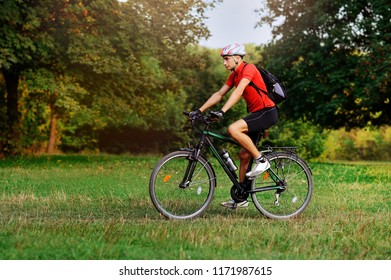 Side view full length picture of a  cyclist at the forest