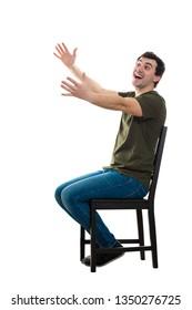 白い背景にコピースペースを持つ古い友人に挨拶するように、椅子に座った興奮した気軽な若い男性の全身像が両腕を伸ばして抱きしめます。