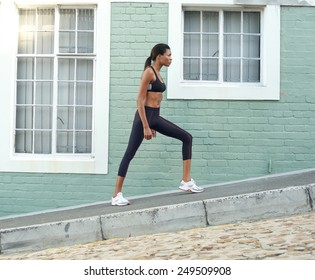 Side view full length portrait of a young african american sports woman stretching legs