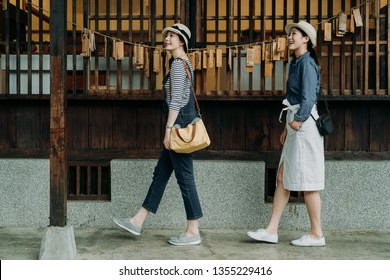 side view full length two asian women tourist visiting in japanese style wooden house with zen garden looking up enjoy nature spring view. young girls friends walk in walkway by wood hope cards wall