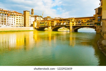 Side view in full sunlight of medieval stone bridge Ponte Vecchio over Arno river, Florence, Tuscany, Italy.