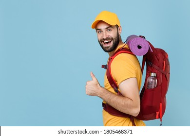 Side view funny traveler young man in yellow casual t-shirt cap with backpack isolated on blue background. Tourist traveling on weekend getaway. Tourism discovering hiking concept. Showing thumb up