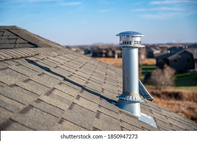 side view of a Galvanized metal chimney exhaust on  asphalt roof with a rain cap