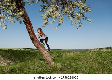 Side view of girl climbing tree trunk against cloudless blue sky while spending time on sunny summer day in nature