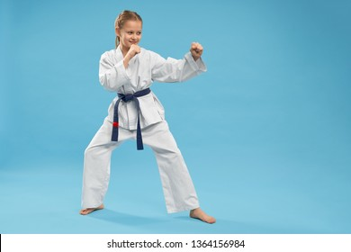 Side view of girl doing martial arts on blue isolated background. Active teenager in white kimono looking at opponent and fighting in studio. Child doing sport and exercising. Concept of combat.
