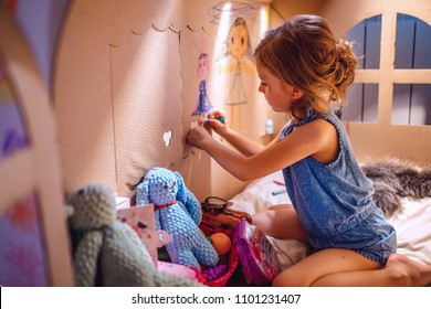 Side view of girl drawing with crayon on wall of carton house sitting inside and having fun at home.