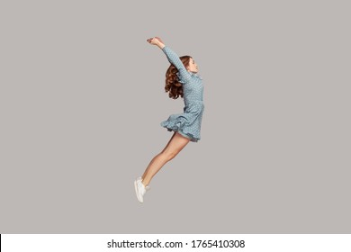 Side view girl in dress levitating hovering in mid-air with raised hands, model looking away concentrated focused, jumping trampoline gaining speed. indoor studio shot isolated on gray background