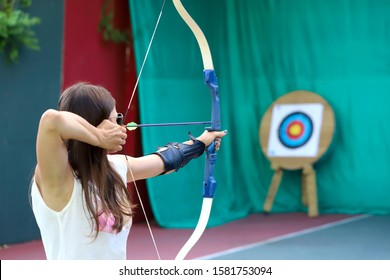 Side view of a girl during archery. Cropped shot, horizontal, close-up. Sport and hobby concept.