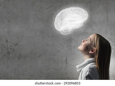 Side view of girl of school age looking at brain above