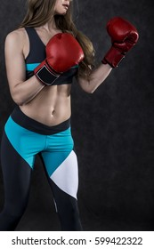 Side view of a girl wearing blue and black sportswear and red boxing gloves making a punch.