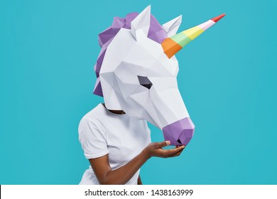 Side view of girl in white shirt wearing papercraft and standing on blue isolated background in studio. Trendy young female posing with colorful unicorn. Concept of happiness and entertainment.