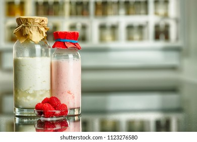 side view of glass bottles with a homemade raspberry smoothie with kefir yogurt and regular kefir yogurt a, plate with raspberry with paper covers and kitchen shelf with spices in the background
