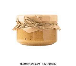 Side view of glass jar with nut butter, hummus or sesame paste tahini with paper covered cap. Food ingredient isolated on white background