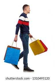 Side view of going man with shopping bags. guy in motion. backside view of person. Rear view people collection. Isolated over white background. Stylish guy thoughtfully carries purchases.