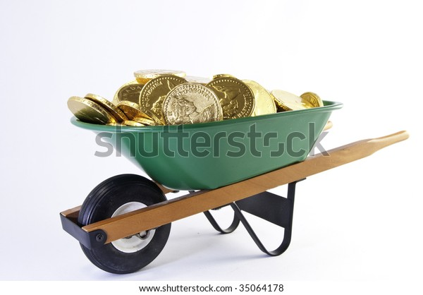 Side view of gold coins in a green wheel barrel.It is on a white background.