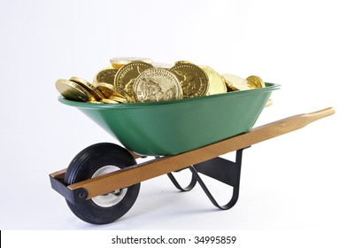 Side view of gold cooins filling a green wheel barrel.It is ona white background.