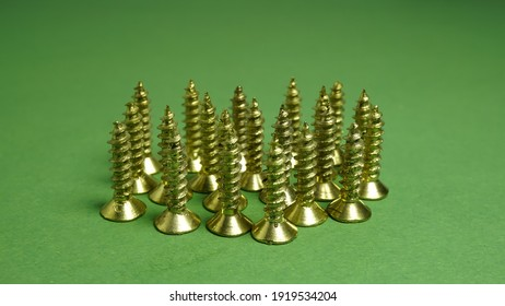 Side view of Golden color slot drive Phillips flat head screw selective focus on some screws on the front isolated on green background. All stand with upward tip and head down on the surface