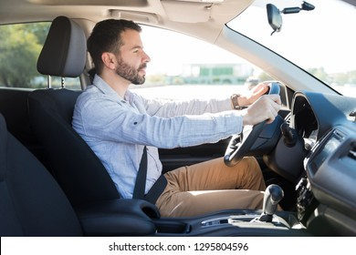 Side view of good looking man driving a car and paying attention to the road