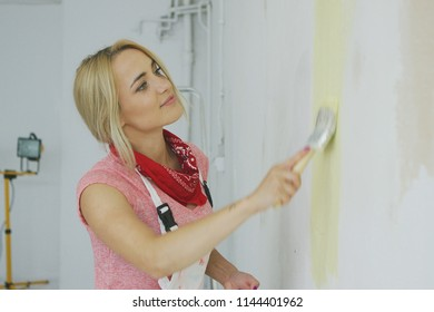 Side view of gorgeous blond pleased female in pink shirt painting with brush plastered wall in pastel yellow color