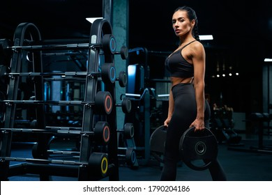 Side view of gorgeous brunette female bodybuilder with braids posing near stand with sports equipment and holding weights. Srtong woman with muscular body posing in empty gym, looking at camera.