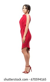 Side view of gorgeous smiling woman in red evening gown looking at camera.  Full body length portrait isolated on white studio background.