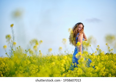 Side view gorgeous young female in stylish blue sundress touching curly hair and looking at camera while standing on blossoming meadow under clear sky in countryside
